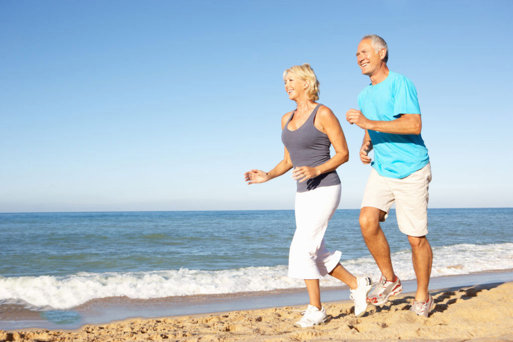 Older man and woman jogging on the beach and smiling.